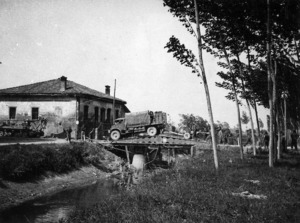 Truck and soldiers of 2nd NZEF, 25 Battalion, B Company, crossing the Scissors bridge, before San Giorgio, Italy