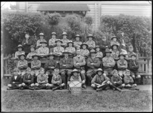 Outdoors in a park area with wooden building behind, group portrait of the Saint Saviour's Boy Scouts Troop, with boys and adults in scout uniforms with an Anglican Priest, bugle, drum and English flag, with 30th October 1920 sign in front, Christchurch