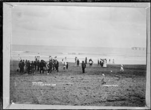 Crowd of people, including a brass band, at the beach at Opunake - Photograph taken by David Duncan