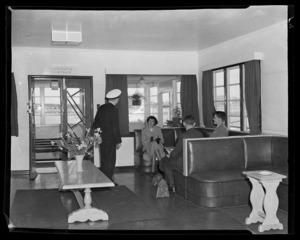 Unidentified people waiting in lounge area, possibly a airport lounge, unknown location
