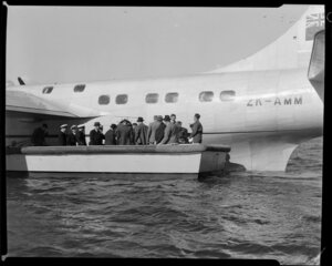 Unidentified passengers and Tasman Empire Airways Limited crew board the Short S.45 Solent flying boat, R.M.A Araragi (ZK-AMM), from a small boat drawn up alongside it, Evans Bay, Wellington