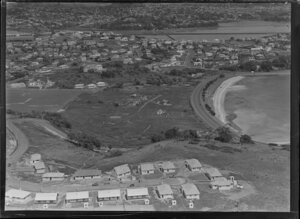 Orakei, Auckland, view of Maori settlement at Orakei Domain, Okahu Bay, with beach and Tamaki Drive with several houses and meeting house on scrubland foreground, residential houses surround with Hobson Bay beyond