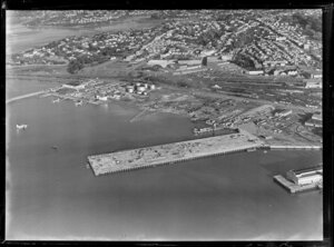 Auckland City water front, showing new wharf area under construction with float plane on harbour, Tamaki Drive and Quay Street, railway yard, views to Parnell and Hobson Bay beyond