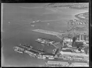 Auckland City water front, showing new wharf area under construction, with commercial buildings and ships at other wharfs, Tamaki Drive and Hobson Bay beyond